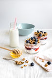 Cooking breakfast with granola and berries on white kitchen background Royalty Free Stock Photos