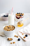 Cooking breakfast with granola and berries on white kitchen background Royalty Free Stock Photo