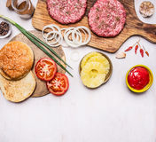 Cooking burger concept buns, cutlet of minced meat, onions, tomatoes, sauce border ,place for text  on wooden rustic background to Stock Photos