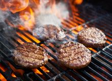 Cooking burgers on hot grill with flames stock photo