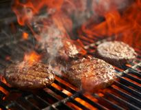 Cooking burgers on hot grill with flames royalty free stock photo