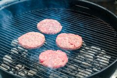 Cooking burgers on hot grill with flames stock photography