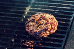 cooking burgers on hot grill with flames royalty free stock image
