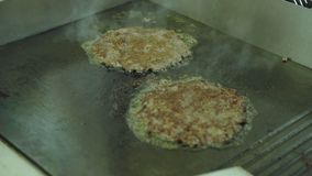 Cooking burgers. Juicy cutlets fried in a professional pan in the kitchen. stock footage