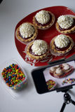Cooking cakes at home. Cooking cakes. Shooting the process on a smartphone. On the table is a plate with ready-made cakes. Smartphone on a tripod Royalty Free Stock Photos
