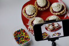 Cooking cakes at home. Cooking cakes. Shooting the process on a smartphone. On the table is a plate with ready-made cakes. Smartphone on a tripod Royalty Free Stock Image