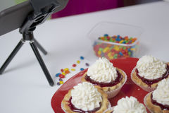 Cooking cakes at home. Cooking cakes. Shooting the process on a smartphone. On the table is a plate with ready-made cakes. Smartphone on a tripod Royalty Free Stock Images