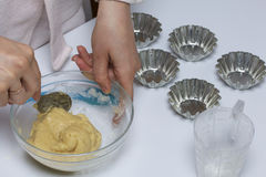 Cooking cakes at home. Cooking cakes. The woman is mixing the dough with a spoon. Next a glass with flour Stock Photo