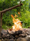 Cooking in caldron. Cooking in the sooty cauldron on the open fire in woods royalty free stock photo