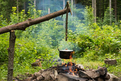 Cooking in caldron. Cooking in the sooty cauldron on the open fire in woods stock images