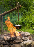 Cooking in caldron. Cooking in the sooty cauldron on the open fire in woods royalty free stock images