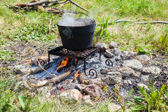 Cooking on a camp fire outdoors in sunny day Stock Photography