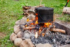 Cooking camp food in cauldrons on open fire Stock Image