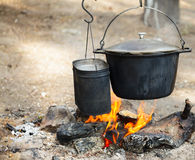 Cooking camp food in cauldrons on open fire Royalty Free Stock Images