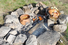 Cooking on Campfire. Cooking a peace of chicken meat on a plane stone and soup in a ceramic pot on bonfire Royalty Free Stock Photography