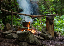 Cooking on campfire. Camping kettle over burning campfire royalty free stock photo