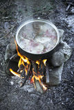 Cooking on campfire. Cooking food using a campfire stock photo