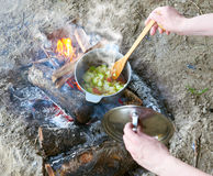 Cooking on campfire at picnic, food prepared in pot on wood, potatoes and tomatoes, healthy vegetarian food, woman hands with spoo Stock Photography