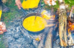 Cooking on campfire. Preparation of scrambled eggs. Stock Images