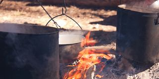 Cooking in a camping trip, outdoor kitchen. Boiling water in a camp pot over an open fire on charcoal. Cooking in a camping trip in the camp. Bright flame on royalty free stock photos