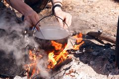 Cooking in a camping trip, outdoor kitchen. Boiling water in a camp pot over an open fire on charcoal. Cooking in a camping trip in the camp. Bright flame on royalty free stock photography