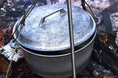 Cooking in cauldron on campfire at forest. Cooking in sooty cauldron on campfire at forest Stock Photos