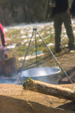 Cooking in cauldron on campfire at forest. Cooking in sooty cauldron on campfire at forest Stock Photo