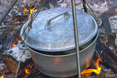 Cooking in cauldron on campfire at forest. Cooking in sooty cauldron on campfire at forest Royalty Free Stock Photos