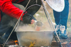 Cooking in cauldron on campfire at forest. Cooking in sooty cauldron on campfire at forest Royalty Free Stock Photography