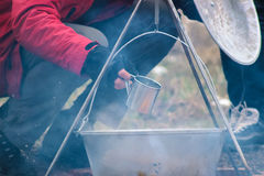 Cooking in cauldron on campfire at forest. Cooking in sooty cauldron on campfire at forest Stock Photography