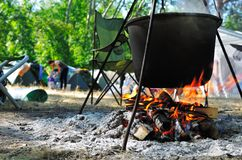 Cooking in a cauldron. On a camping background stock photo