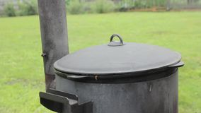 Cooking in a cauldron outside on a wood stove , steam from under the lid.  stock video