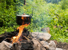 Cooking in cauldron. Cooking in the sooty  cauldron on the open fire in woods Stock Images