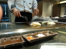 Cooking. Chef cooking food in Japanese restaurant royalty free stock images