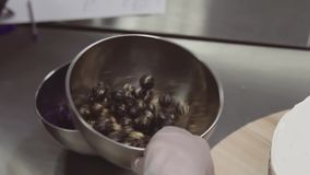 Cooking chef hand shaking metal bowl, mixing blueberries with brown sugar stock footage
