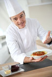 Cooking chef in the kitchen with spaghetti bolognese Royalty Free Stock Image