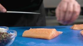 cooking Chef-kok die de zalm, scherpe vissen door mes snijden, Snijdende zalmfilets stock videobeelden