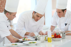 Cooking chef showing skills to apprentices Stock Photography