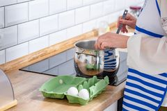 Cooking chicken eggs in pot on electric stove. Woman Cooking chicken eggs in pot on electric stove royalty free stock photos