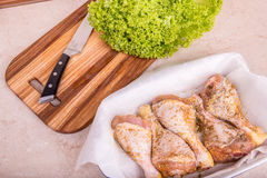Cooking chicken legs with spices and garden greens Stock Photos