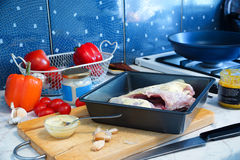 Cooking chicken. the mess on the kitchen table. Chicken on baking sheet. tomatoes, peppers and garlic lie nearby. jars with sauces. the mess on the table Royalty Free Stock Images