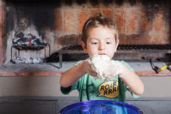 Cooking with childs. A child preparing pizza in a kitchen Royalty Free Stock Images