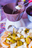Cooking chocolate fondue with  fruits Royalty Free Stock Photo