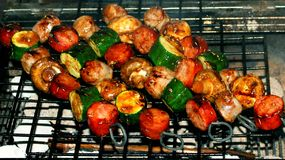 Cooking chorizo zucchini  mushroom skewers over hot coals on  a barbecue Stock Photography