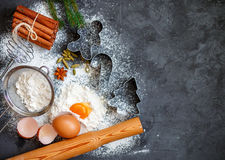 Cooking Christmas biscuits and gingerbread. Ingredients for the dough and the spices on the table. Flour, eggs, cinnamon sticks, cardamom, star anise and brown Royalty Free Stock Photo
