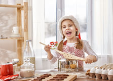 Cooking Christmas biscuits. Little girl cooking Christmas biscuits Stock Photo