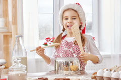 Cooking Christmas biscuits. Little girl cooking Christmas biscuits Stock Photos