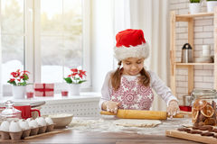 Cooking Christmas biscuits. Little girl cooking Christmas biscuits Royalty Free Stock Photos