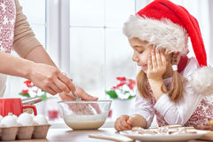 Cooking Christmas biscuits. Mother and daughter cooking Christmas biscuits Stock Photo
