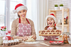 Cooking Christmas biscuits. Mother and daughter cooking Christmas biscuits Royalty Free Stock Photos